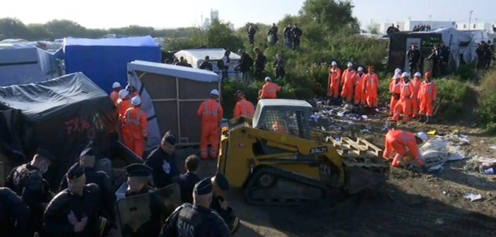 Crews start dismantling French camp while migrants remain